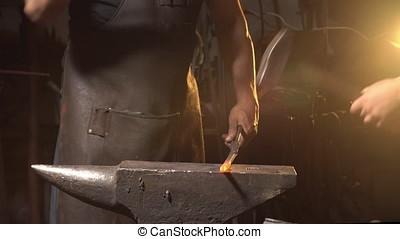 blacksmith forges on the anvil. brutal man working at the forge with metal. Blacksmith, holds molten metal on an anvil with a spark firework