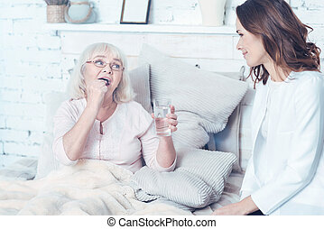 Responsible nurse caring about aging patient at home