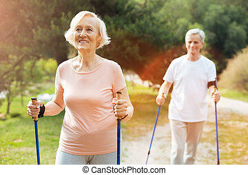 Happy elderly woman hiking with her husband