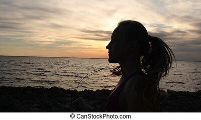 Sporty fitness woman running on seaside at sundown