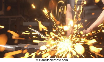 Sparks flying at the camera. A man working angular grinding...