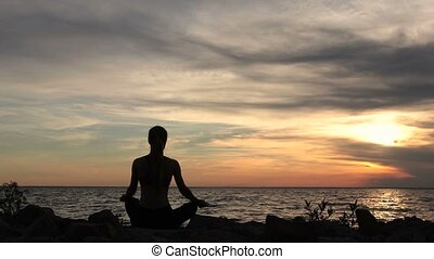 Yoga woman in lotus pose on beach at sunset - Back view of...