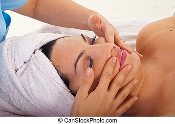 Beautician massaging woman face