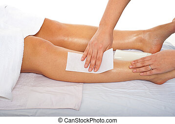 Waxing leg - Beautician waxing woman legs in a spa salon