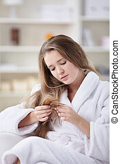 Hair Care - A young girl in a bathrobe looking at the hair...