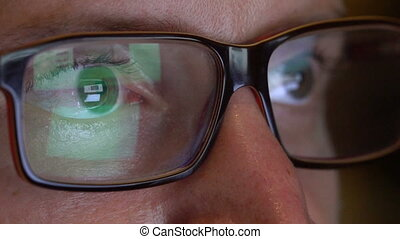 Closeup man's eyes in glasses works on laptop at night -...