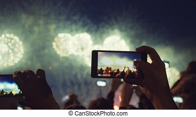 Hands of peoples taking photo to fireworks on smartphone. Close-up. Slow motion