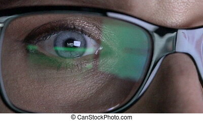 Closeup woman's eye in glasses works on laptop at night -...