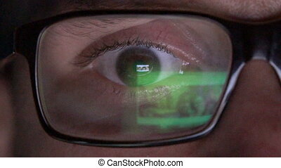 Closeup man's eye in glasses works on laptop at night -...