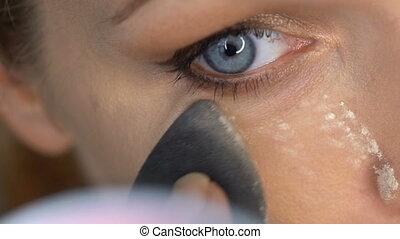 Woman's face applying makeup - Closeup of woman's face...