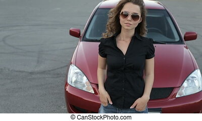 Girl in sunglasses posing against red car background - A...