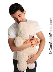 Man hugging a teddy - A man cuddling a teddy bear. White...