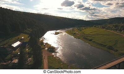 aerial view from a height on the river near the forest -...