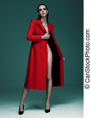 Fashion model with wet hair wearing red long coat on green...