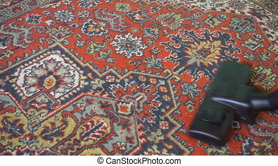Vacuum cleaner cleaning the carpet, a man vacuuming the red...