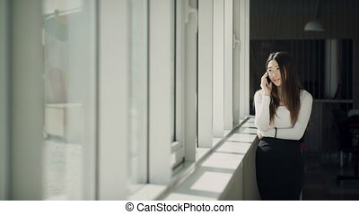 Attractive asian woman talks on white mobile phone in office near window.