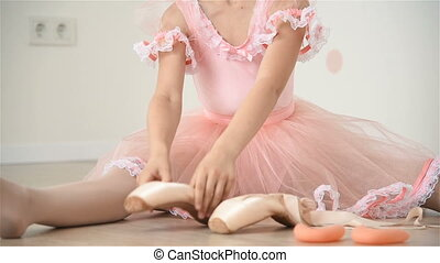 Ballerina Gathers Her Pointe - Little Ballerina Girl Sitting...