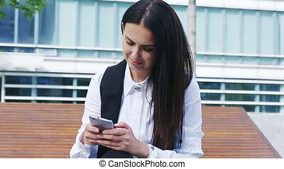 Attractive female using cellphone sitting on the bench