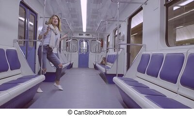 Young woman dancing in subway train - Happy young woman...