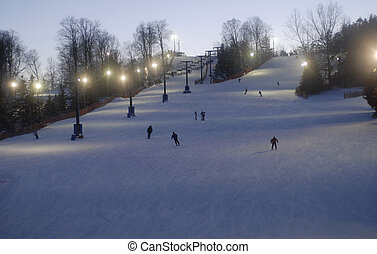 night time skiing and snowboarding at a small ski hill in...