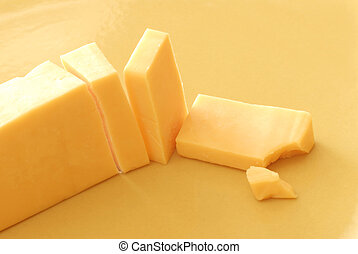 sliced cheddar cheese with a small nibble out of the corner