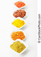 Alternation of grounded spices in a row on tablecloth above...