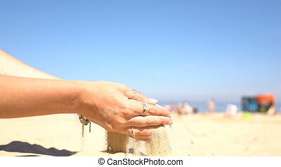 Sand pouring from the hands of a woman on the beach.