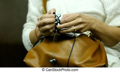 The woman goes to the subway and unravels the headphones