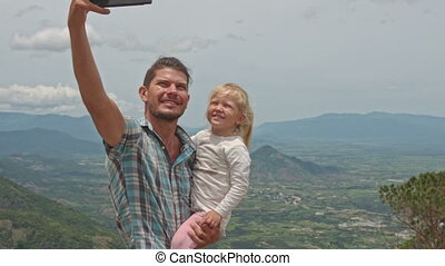 Father Holds Little Blond Daughter Makes Selfie against...