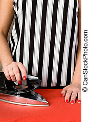 Female hands with red nails and an old electric iron.
