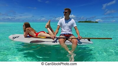 v07291 Maldives white sandy beach 2 people young couple man woman paddleboard rowing on sunny tropical paradise island with aqua blue sky sea water ocean 4k