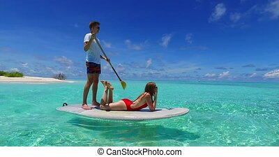 Maldives white sandy beach 2 people young couple man woman paddleboard rowing on sunny tropical paradise island with aqua blue sky sea water ocean 4k