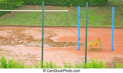 Heavy rain on outdoor tennis or volleyball court and empty...