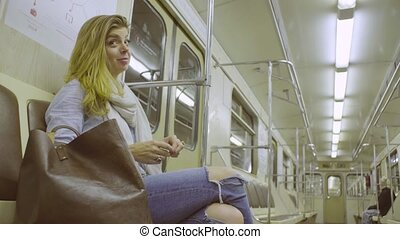 Young woman sitting in subway train - Happy young woman...