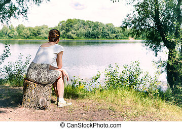 Woman Sitting Close to the River - A woman is sitting close...