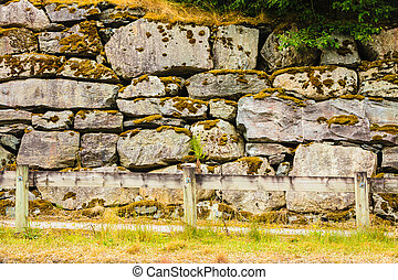 Fence and narrow path along wet stone wall rock solid