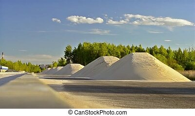 Mountains of white sand lie on side of road. Construction of...