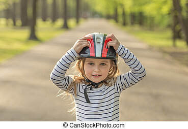 Small girl in helmet for roller outside