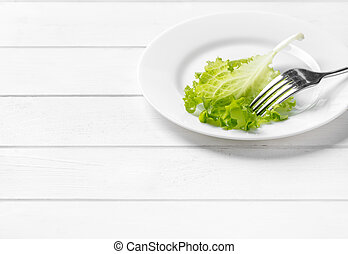 White plate with a leaf of lettuce - White plate with a...