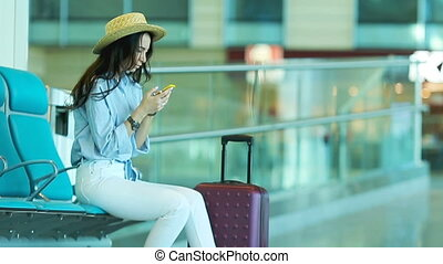 Young woman in an airport lounge waiting for flight...