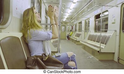 Young woman sitting in subway train, listening music and...