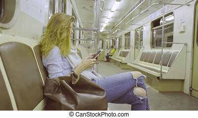 Young woman sitting in subway train and listening music