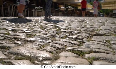 Stone pavement video made from the ground level with cafe...