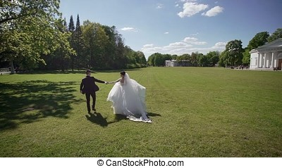 Bride and groom walking in a field at sunny day