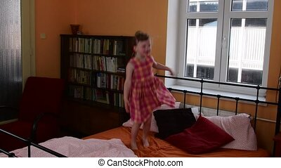 A cute small girl jumping on the bed. Parents bedroom and her daughter is jumping on the bed