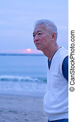 Asian senior standing alone and thinking at mornign beach...