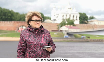 Adult woman takes photos using silver smart phone