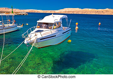 Floating boat on turquoise sea in Velebit channel, with...