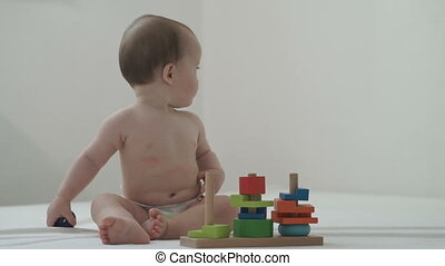 A little child plays with a developing toy