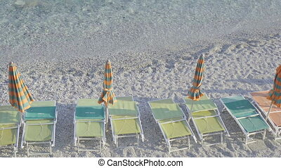 Sunbeds and umbrellas at beautiful european seashore in...